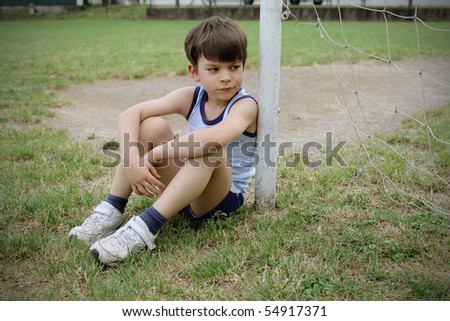 Sad child sitting against a football door - stock photo