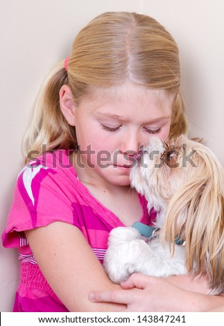 sad child sitting in corner with dog licking her face trying to comfort her. - stock photo