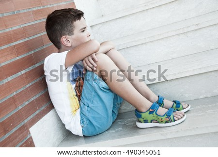 Sad child sitting on stairs