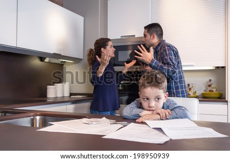 Sad child suffering and his parents having hard discussion in a home kitchen by couple difficulties. Family problems concept. - stock photo
