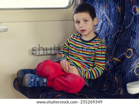 Sad child traveling on train, sitting on a seat.  - stock photo