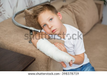 Sad child with a broken arm in the home environment . The cast on the hand of a little boy. Injury to a child is bored at home.