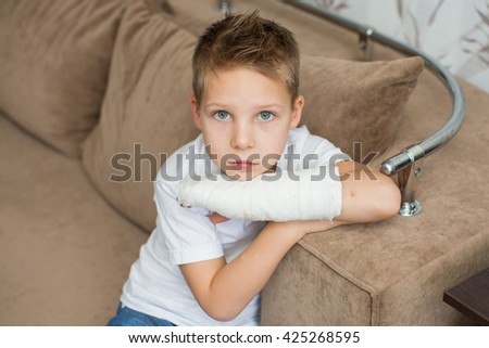 Sad child with a broken arm in the home environment . The cast on the hand of a little boy . Injury to a child is bored at home. - stock photo