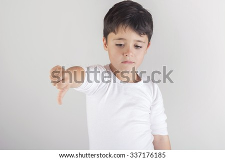 sad child with his finger downward - stock photo