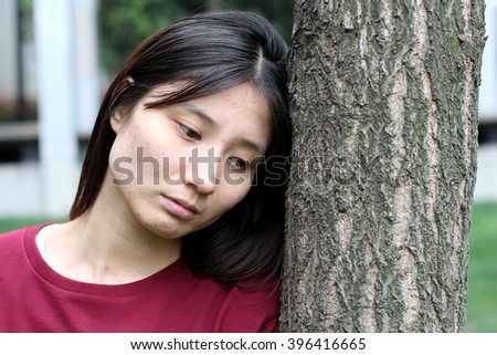 Sad Chinese Girl Leaning on the Tree - stock photo