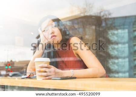Sad Chinese woman in a cafe in London. She is sitting alone at a table facing the window, looking out and holding her head with one hand. Sadness and solitude concepts.