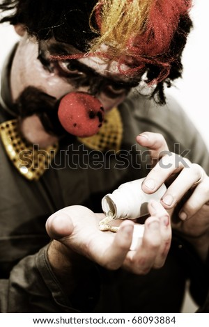 Sad Clown Desperately Pours Out Happy Pills Into His Hand To Help Cure His Sorrow - stock photo