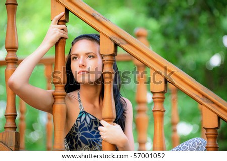 Sad concerned young dark-haired woman at handrail. - stock photo