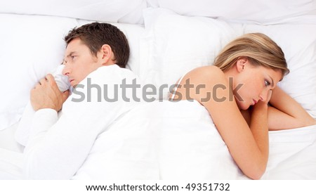 Sad couple having an argument lying on bed - stock photo