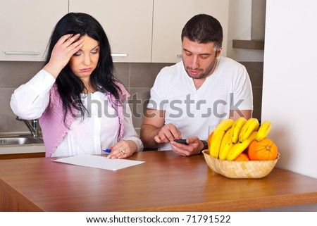 Sad couple having difficult to calculate their expenses - stock photo
