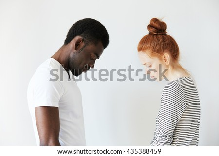 Sad couple looking down with their heads bowed in front of each other. Side view portrait of two sorrowful people: young Caucasian redhead girl and Afro-American melancholic man. Negative emotions. - stock photo
