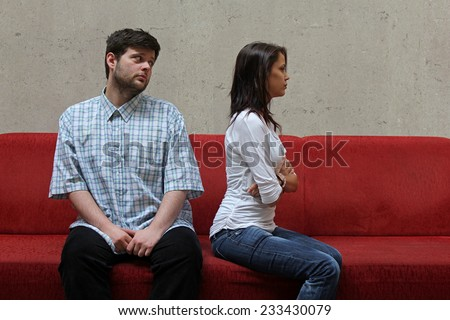 sad couple sitting on a red sofa, young man hopefully watching his girlfriend while waiting for her forgiveness - stock photo