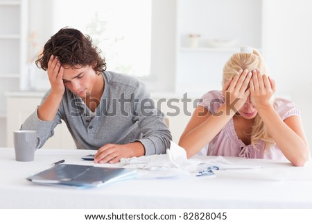 Sad couple while accounting in their living room - stock photo