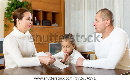Sad couple with kids and bills at table - stock photo