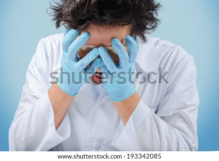 Sad crazy man doctor holds his face - stock photo