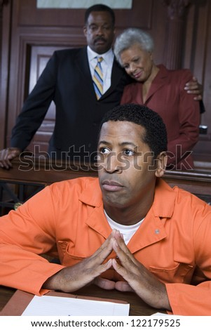 Sad criminal sitting in court with parents standing behind him - stock photo