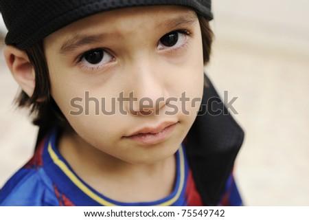 sad cry kid boy is looking at camera - stock photo