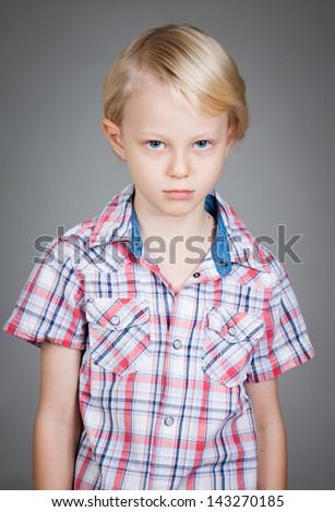 Sad cute grumpy young boy looking at the camera - stock photo
