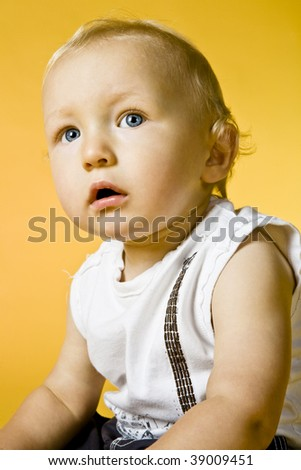 Sad cute little boy posing on yellow background.