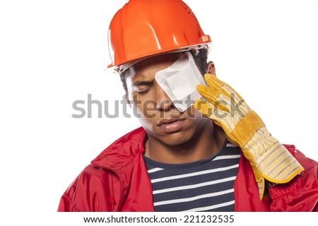 sad dark-skinned worker with helmet and injured eye - stock photo