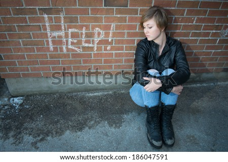Sad, depressed girl outside school, with red brick background - stock photo