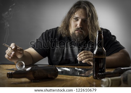 sad depressed man at a table with alcohol bottles, cigarettes and what looks like cocaine - stock photo