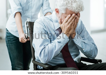 Sad depressed man in wheelchair with head in hands, a woman is taking care of him - stock photo