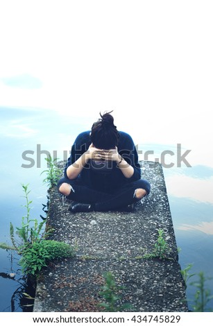 Sad depressed teenage girl sitting on a dock. Depression concept. - stock photo