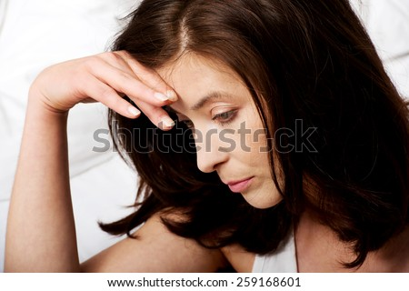 Sad depressed woman sitting on bed. - stock photo