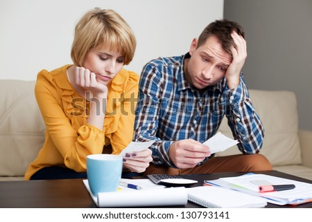Sad, depressed young couple paying bills. - stock photo