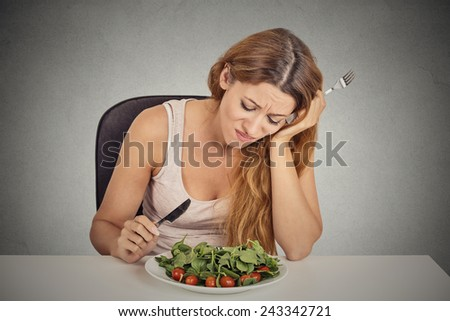 sad displeased young woman eating salad isolated grey wall background. Negative human face expression emotion. - stock photo