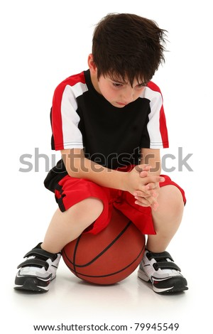 Sad elementary school boy sitting on basketball sad crying expression on face. - stock photo