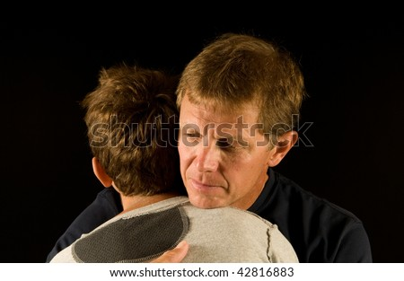 Sad embrace - father hugs his preteen son (consoling, making up after argument, or otherwise comforting)