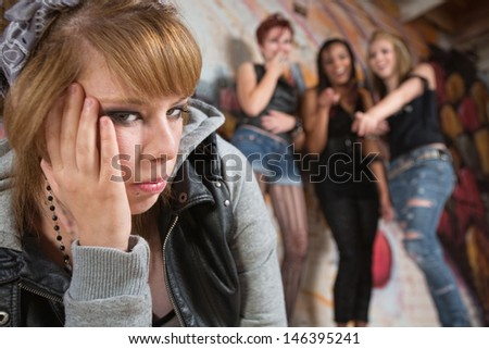 Sad European young woman harassed by group of teenagers - stock photo
