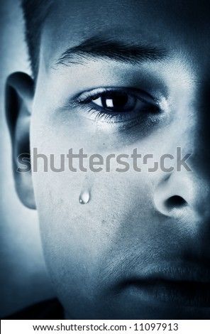 Sad face close-up - a tear is running down a cheek - stock photo