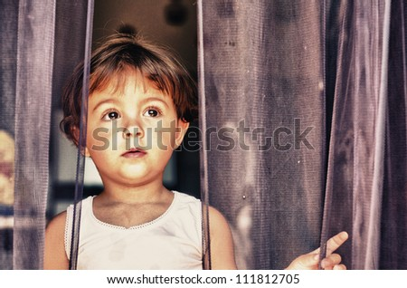 Sad face expression of Baby behind the Curtain - Italy - stock photo
