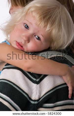 sad face of two years old blonde girl on shoulder of her mother - stock photo