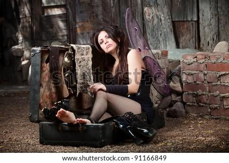 Sad fairy smokes cigar in a rustic scene - stock photo