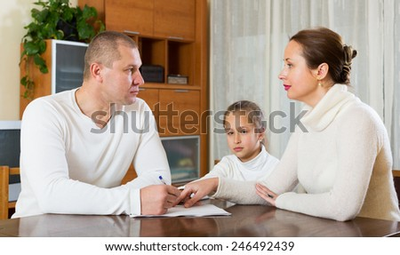 Sad family of three with documents at home - stock photo