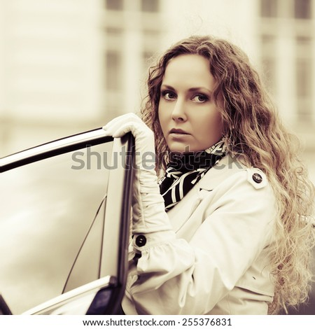 Sad fashion woman with long curly hairs at the car  - stock photo
