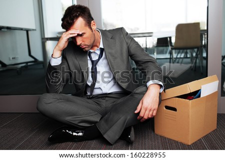 Sad fired businessman sitting outside meeting room after being dismissed - stock photo