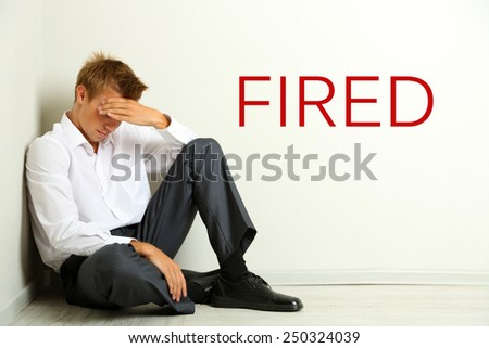 Sad fired office worker sitting on floor on gray wall background - stock photo