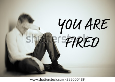 Sad fired office worker sitting on floor on wall background - stock photo