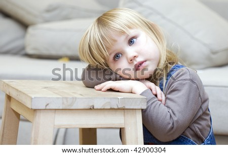 Sad, frighten or thoughtful little girl with blond hair. Sitting on floor, lying on leaning on wooden stool hands face - stock photo