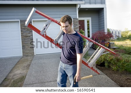 Sad, frowning man standing in front of house holding ladder and hammer. Horizontally framed photo. - stock photo