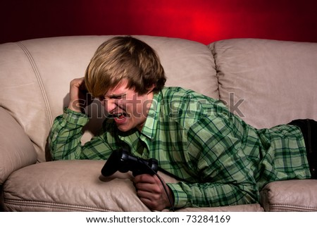 sad gamer on the red background - stock photo