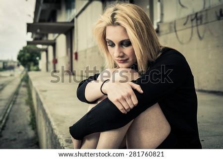 Sad girl alone in urban blight - stock photo