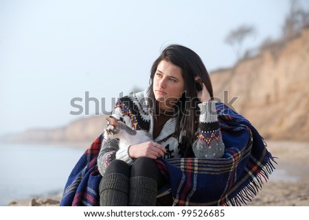 Sad girl and her cat sitting by the seashore
