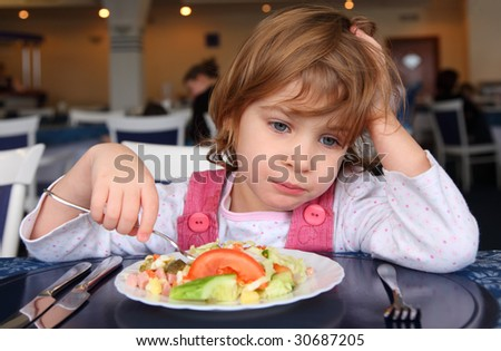 Sad girl behind table in cafe - stock photo