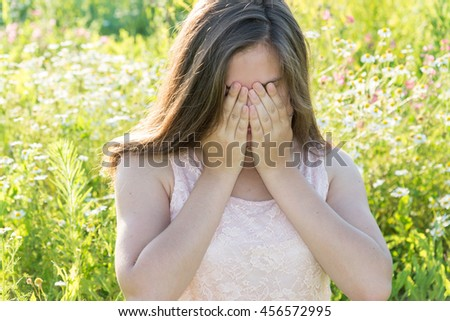 Sad girl covers her face with her hands and weeps - stock photo